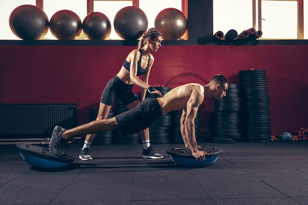 Athletic man and woman with a dumbbells training and practicing in gym.