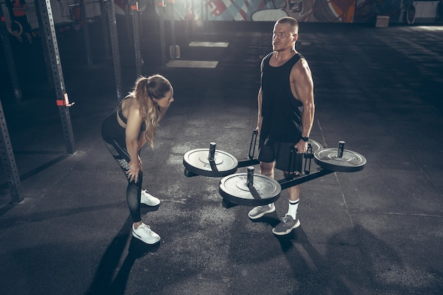 Athletic man and woman with dumbbells
