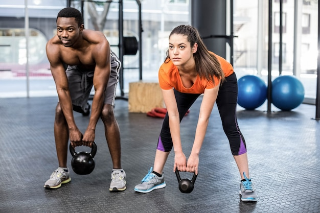 Athletic man and woman working out at gym