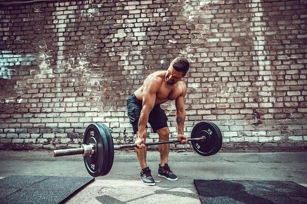 바 벨으로 운동 운동 남자입니다. 힘과 동기 부여. 등 근육 운동