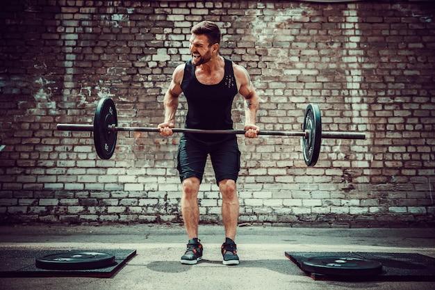 バーベルでワークアウト運動の男。強さと動機。背中の筋肉の運動