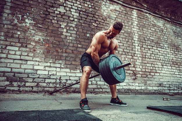 Athletic man working out with a barbell. strength and motivation. exercise for the muscles of the back