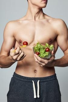 アスリートの男性のトレーニングは、トルソプレートサラダの健康的な食品エネルギーを汲み上げました