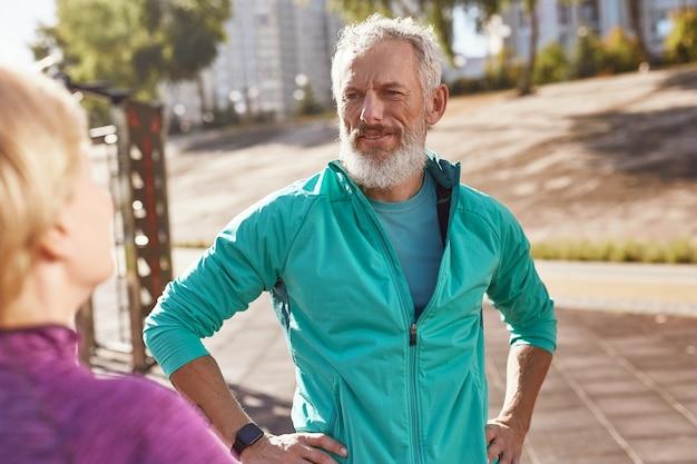 운동복을 입은 성숙한 수염 난 남자가 에서 함께 운동하는 동안 아내와 이야기를 나누었습니다.