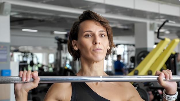 Спортивная (ый) зрелая женщина делает набор упражнений на повторение со штангой, поднимающей ее над головой в тренажерном зале.
