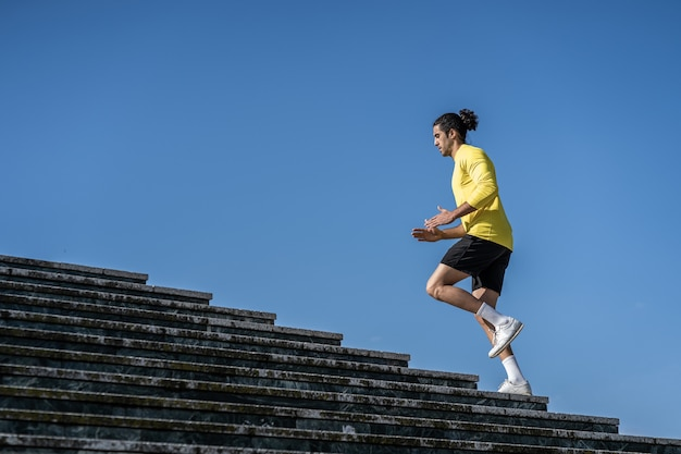 Athletic men, climbing stairs to strength legs. blue sky