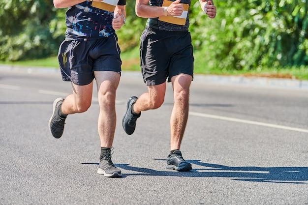 街の道路でスポーツウェアでジョギングアスリートの男性