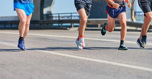 Спортивные мужчины бег в спортивной одежде на городской дороге