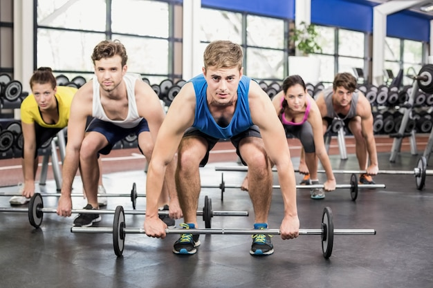 Athletic men and women working out at crossfit gym