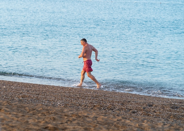 Athletic middleaged man jogging along a beach in the surf