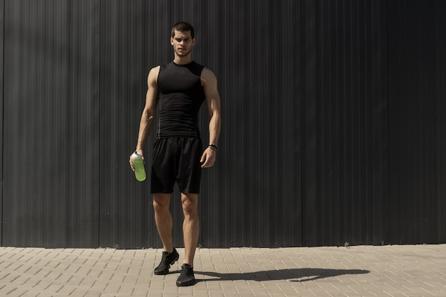 Athletic modern young man posing on a gray metallic wall