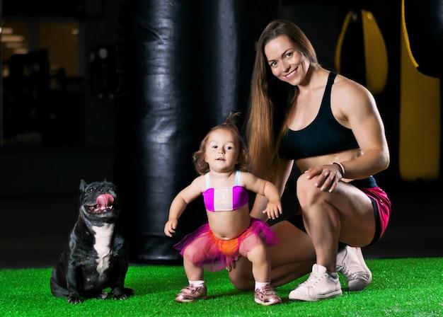 그녀의 작은 딸과 강아지와 운동 어머니