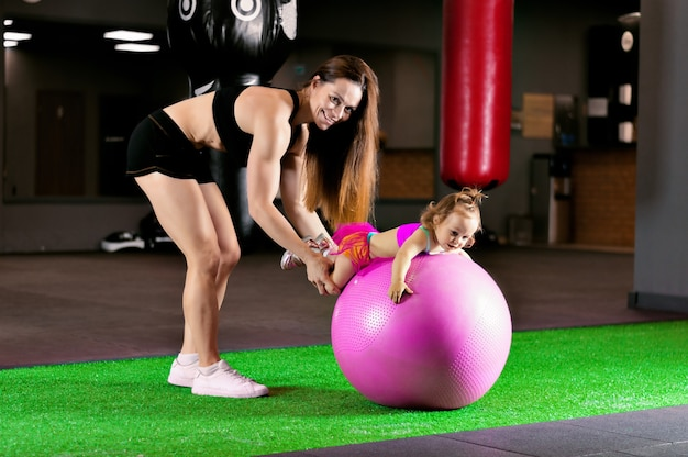 Athletic mother with her little daughter