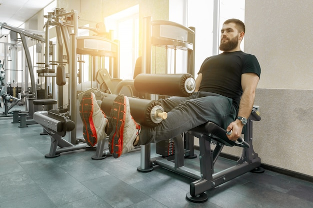Athletic muscular bearded exercising man at gym