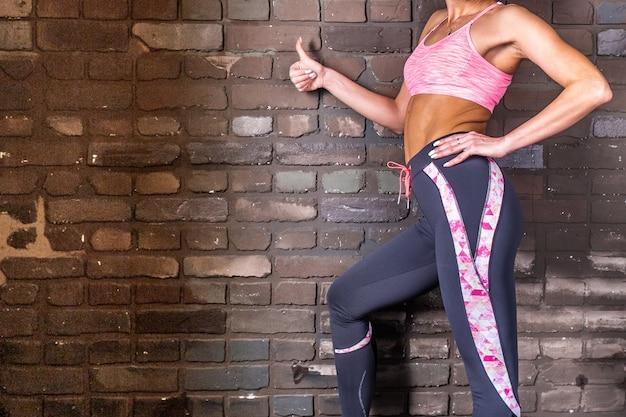꽉 운동복을 입은 젊은 여성의 근육질 배와 엉덩이