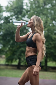 Athletic muscular girl drinking water after training.