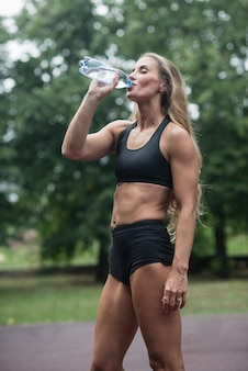 Athletic muscular girl drinking water after training