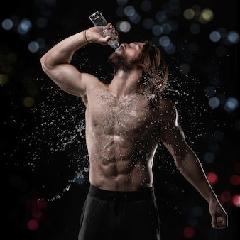 Athletic muscular man drinking water in studio with splashes