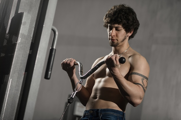 Athletic muscular man training biceps in the gym