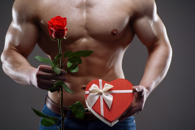 彼の手に赤いバラとギフトボックスを保持している運動の裸の男。バレンタインデーのコンセプト