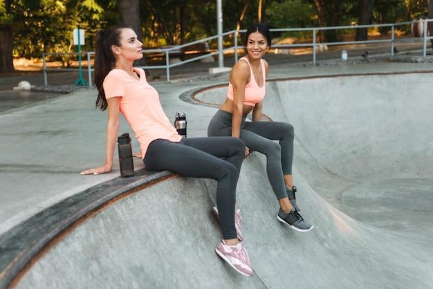 콘크리트 운동장에 물병에 앉아 운동복에 운동 좋은 여성