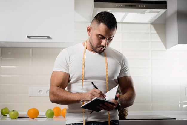 Athletic nutritionist writes in a notebook in the kitchen