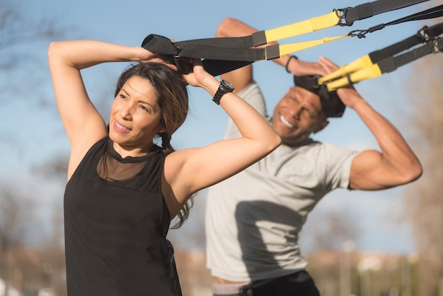 Athletic partners doing biceps and arms exercise with trx fitness straps in park. multi-ethnic people exercising outdoors.