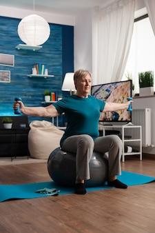 스위스 공에 앉아 태블릿을 사용하여 온라인 에어로빅 운동을 보는 스포츠웨어의 운동 연금
