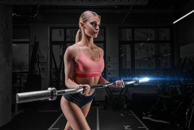 Женщина спортивного телосложения позирует в тренажерном зале со штангой в руках. понятие спорта, фитнеса, здорового образа жизни.