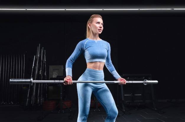 그녀의 손에 바 벨과 함께 포즈 운동 체격 여자. 스포츠, 피트니스, 건강한 라이프 스타일의 개념. 혼합 매체