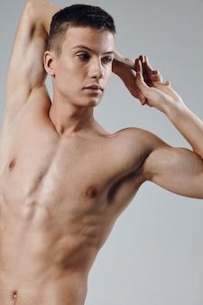 Спортивное телосложение молодой мужчина обнаженный торс серый фон портрет обрезанный вид