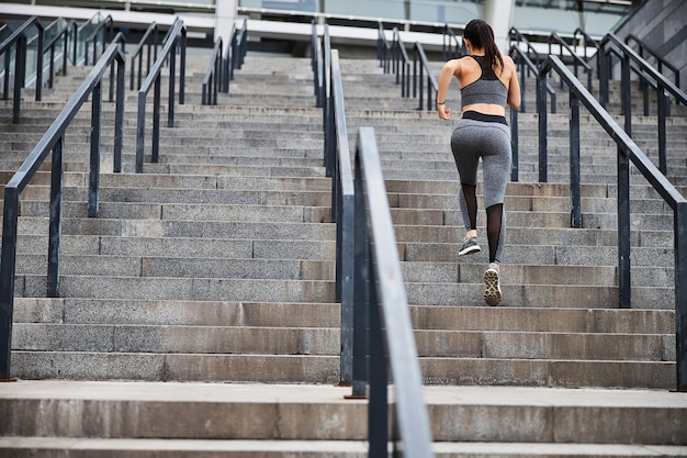 Athletic pretty female is having cardio training outdoors and jogging on steps in urban street