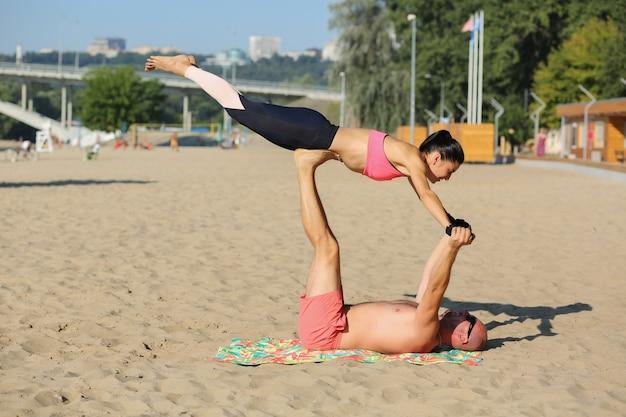 ビーチでヨガを練習している運動のきれいな女性とハンサムな筋肉の男