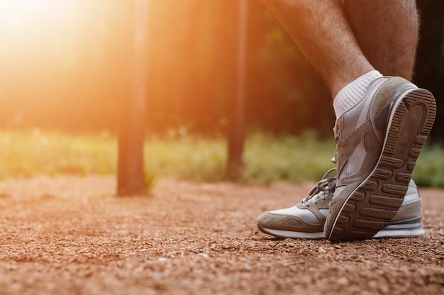 Athletic runner preparing for morning workout in the park, lens flare