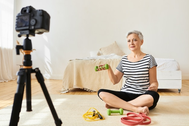 緑のダンベルで床に短い白髪の運動をしているアスレチックシニア女性フィットネスインストラクター、三脚のカメラを介してビデオチュートリアルを記録します。人、年齢、健康的なアクティブなライフスタイル