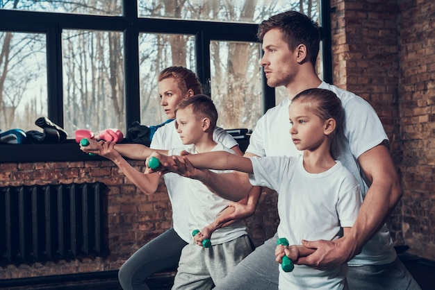 Athletic serious family exercises with dumbbells in the gym.