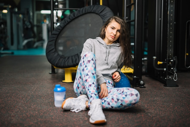 Athletic serious woman sitting near bottle in gym