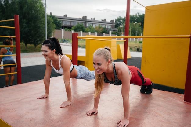 Спортивные, сексуальные девушки синхронно делают отжимания на улице. фитнес, здоровый образ жизни