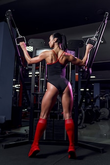 Athletic sexy woman doing exercise using machine in gym - back view
