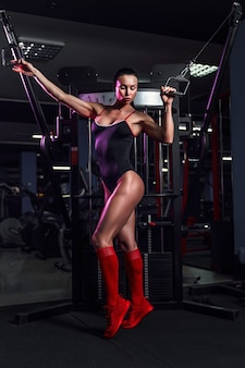 Athletic sexy woman doing exercise using machine in gym - front view.