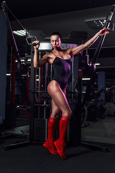 Athletic sexy woman doing exercise using machine in gym - front view