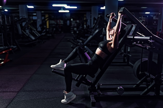 Athletic sexy woman doing exercise using machine in gym - side view