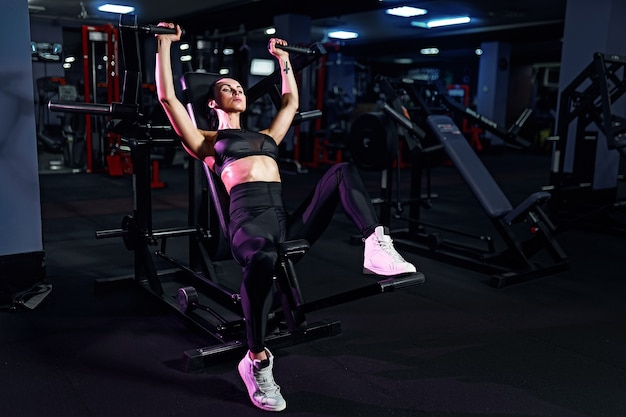 Athletic sexy woman doing exercise using machine in gym