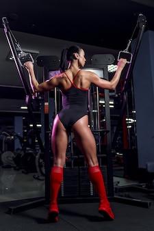 Спортивная (ый) сексуальная женщина делает упражнения на машине в тренажерном зале