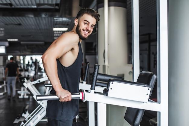 Maschio atletico senza camicia che fa allenamenti su una schiena con una macchina per esercizi di potenza in una palestra