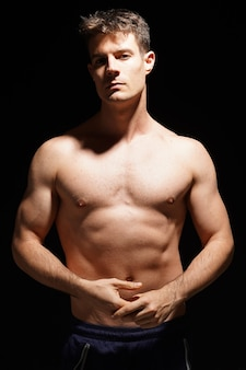 Athletic shirtless male standing confidently over black background