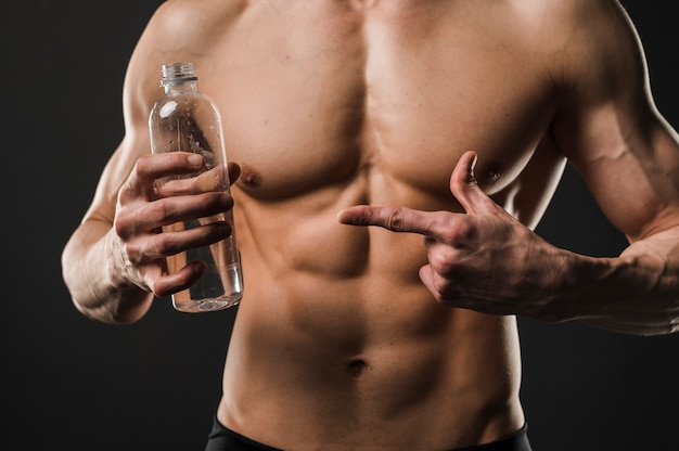 Athletic shirtless man pointing at water bottle
