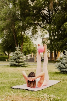Athletic, slender woman in pink clothes and small rubber ball doing pilates on pink mat at dawn in park in summer.