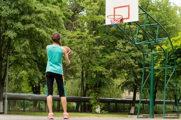 バスケットボールをしている運動のほっそりした少女