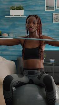 ビデオカメラを使用してオンラインヨガクラスを記録する黒い肌のアスレチックスリムな女性